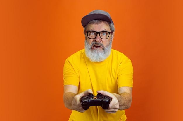 緊張したゲーマー。オレンジ色のスタジオの背景に分離されたデバイス、ガジェットを使用して流行に敏感なシニア男性の肖像画。技術と楽しい高齢者のライフスタイルのコンセプト。トレンディな色、永遠に若さ。あなたのためのコピースペース