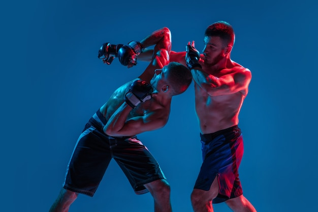 Напряженный. мма. два профессиональных бойца пробивают или боксируют, изолированные на синем фоне студии в неоне. подойдут мускулистые кавказские спортсмены или борющиеся боксеры. спорт, соревнования и человеческие эмоции, реклама.