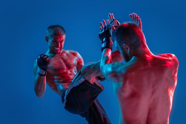 緊張。 mma。ネオンの青いスタジオの背景に分離された2人のプロの戦闘機のパンチまたはボクシング。筋肉質の白人アスリートやボクサーの戦いにぴったりです。スポーツ、競争、人間の感情、広告。