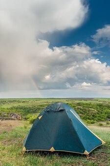 Палатка после дождя, пейзаж с облаками и радугой в голубом небе