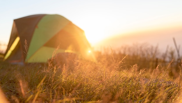 Tent for backpacker outdoor life with summer nature landscape outdoor on sunset with bright sunlight
