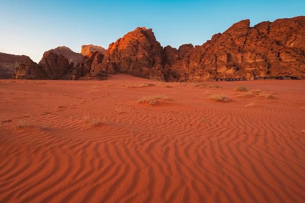 砂の上のパターンでヨルダンのワディラムの赤い砂漠で日没の岩のそばのテントキャンプ