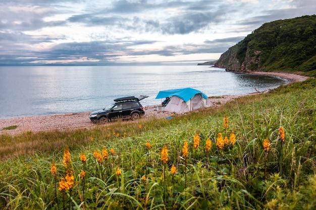 Палаточный кемпинг на берегу моря. черная машина возле палатки.
