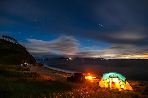 Палаточный лагерь на берегу моря в ночное время.существует некоторый шум от высокого iso.