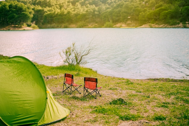 Tent and camping chairs by lake