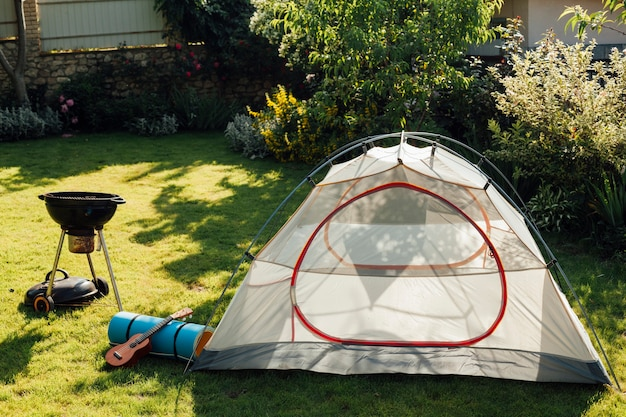 Tent camping with barbecue grill and ukulele on grass