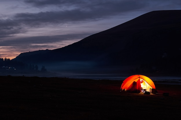 Tent glowing red under a night sky full of stars.