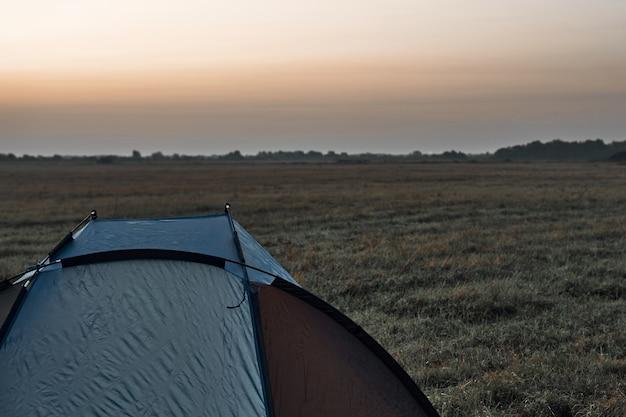 野原のテント、日の出、秋。