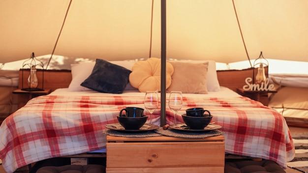 글램핑에서 침대와 접시가 있는 텐트 내부