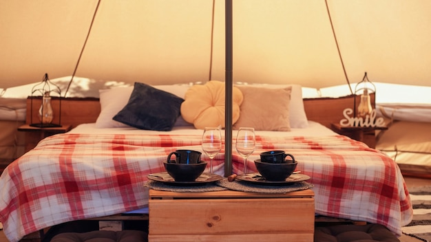 Tent interor with bed and dishes at glamping