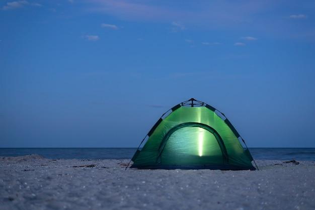 Палатка освещена ночью. кемпинг на берегу моря.