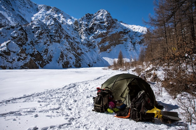 A tent is set up in a high mountain environment