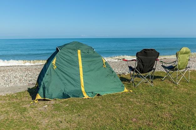 Палатка на пляже с двумя стульями, стоящими на траве. палатка на пляже..поездка в грузию