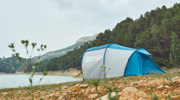 Палатка на берегу озера с лесом и горами