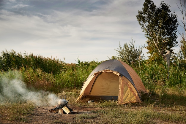 Tent on the shore of the lake near a burning fire with a kettle.