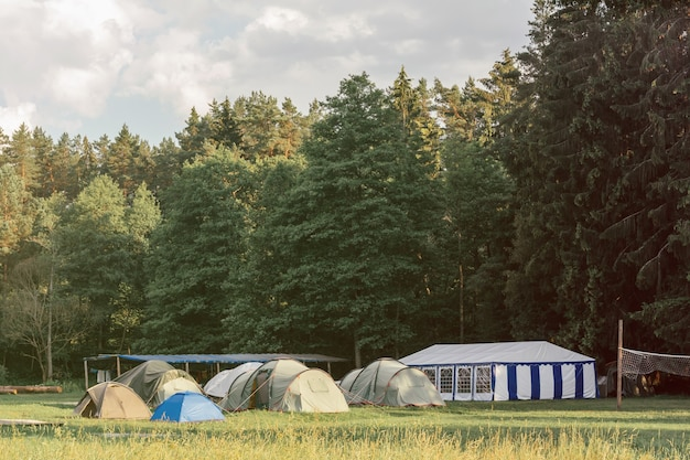 Tent town against backdrop of forest on meadow with pavilion and volleyball net, camping concept