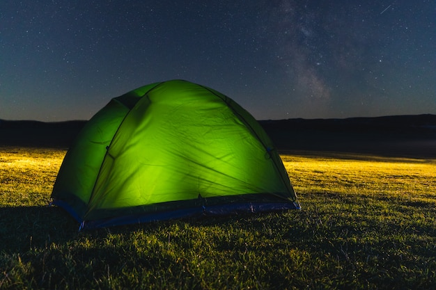 Tent with light on the countryside at night with stars