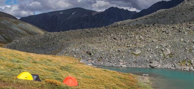 小さな山の湖の岸にあるテント