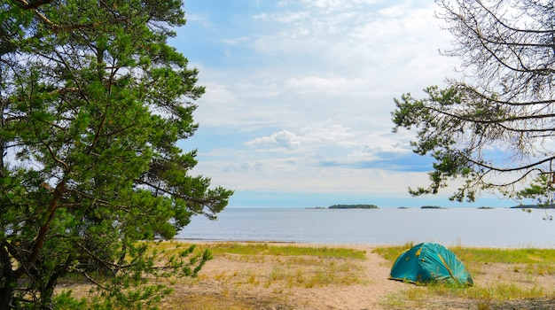 Tents on the sandy shore of the lake.
