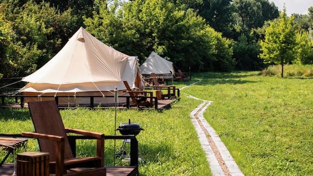 Палатки с деревянными стульями и дорожкой перед ними на глэмпинге. природа, зелень вокруг