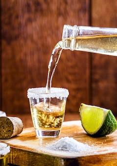 飲み物のグラスを埋めるテキーラボトル。提供されている典型的なメキシコの飲み物。