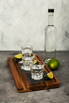 Tequila bottle and shots, limes, salt on wooden board