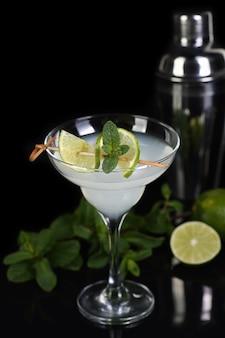 テキーラ、柑橘類の酒、ライムジュース-これはマルガリータカクテルです。ミントの小枝とライムのaはガラスを飾ります。暗い不機嫌そうな食べ物