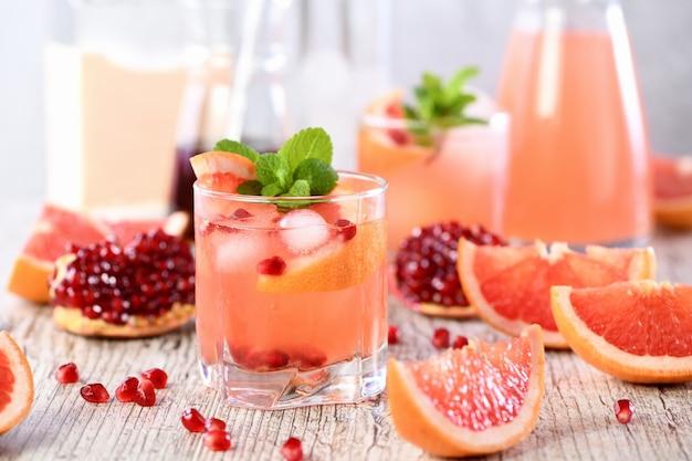 ザクロとグレープフルーツジュースのテキーラカクテル、ミントの新鮮な小枝の香りで染められています