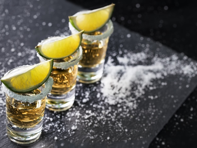 Tequila glasses with lime standing in row