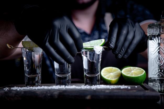 Текила золото, мексиканский, алкоголь в рюмках, лайм и соль, тонированное изображение, выборочный фокус