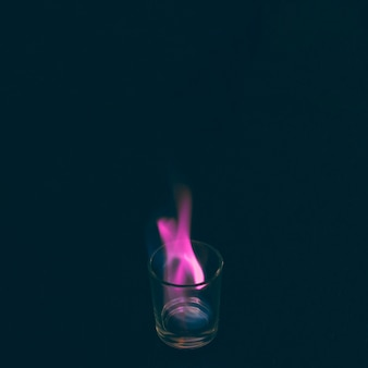 Tequila shot glass burning with pink flame