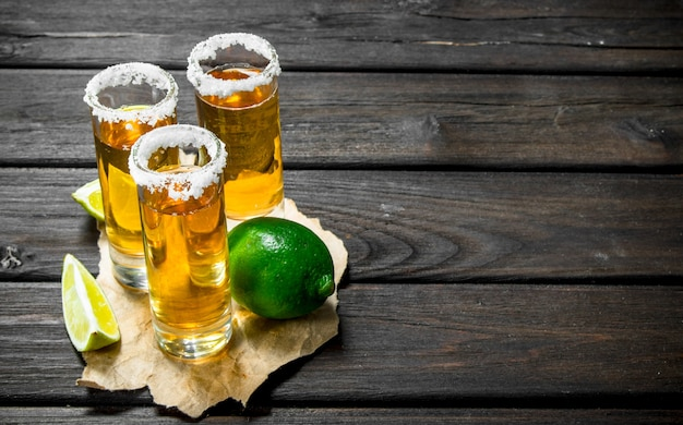 Tequila in a shot glass on paper with lime on wooden table