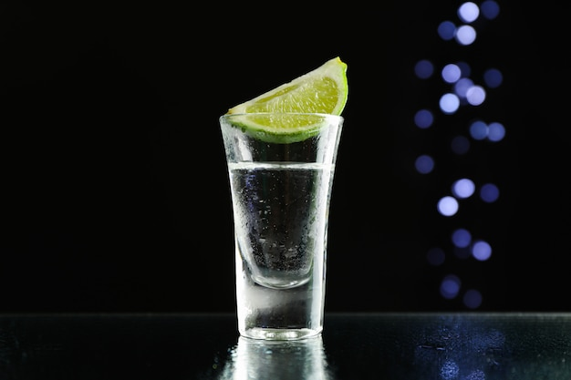 Tequila shot with lime against black with blurred lights