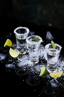 Tequila shot with lime and salt on black background