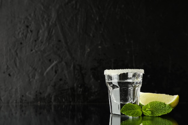 Tequila shot with lime, salt and mint against black