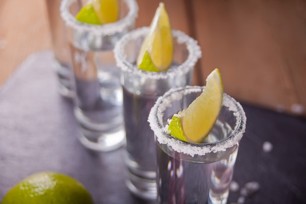 Tequila shot with lime and sea salt on black tray, selective focus