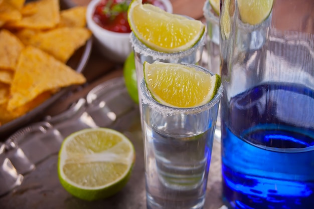 Tequila shot with lime and sea salt and blue bottle on tray