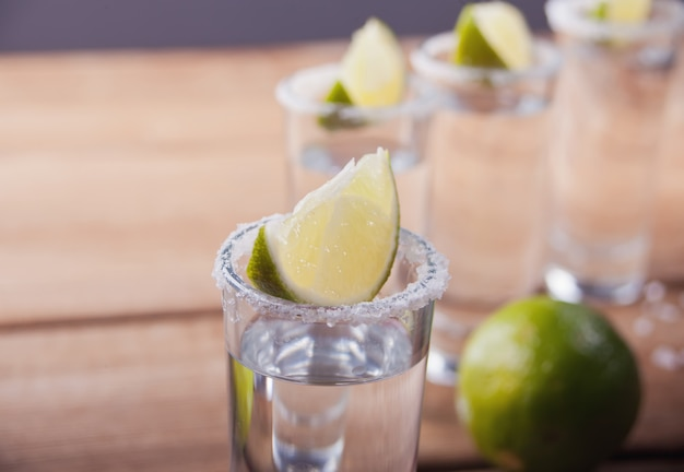 Tequila shot with lime and sea salt on old wooden table, selective focus