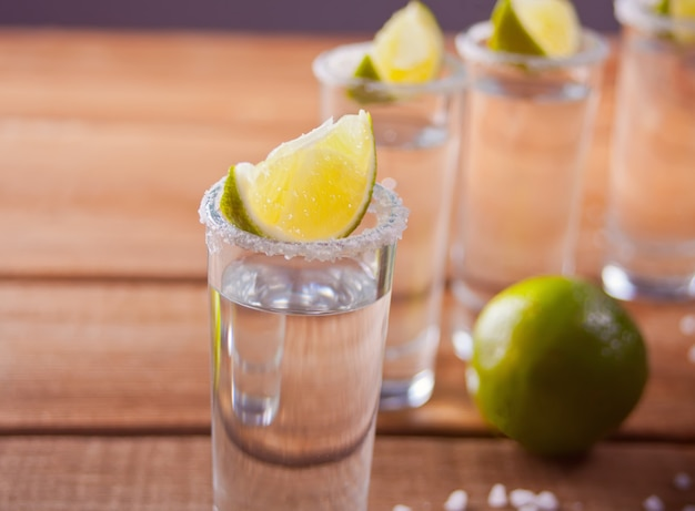 Tequila shot with lime and sea salt onwooden table