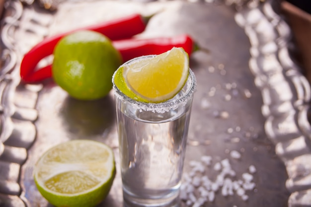 Tequila shot with lime and sea salt on tray