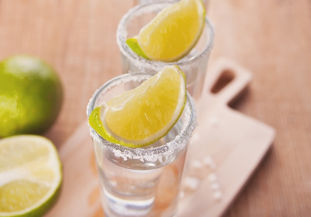 Tequila shot with lime and sea salt on wooden board