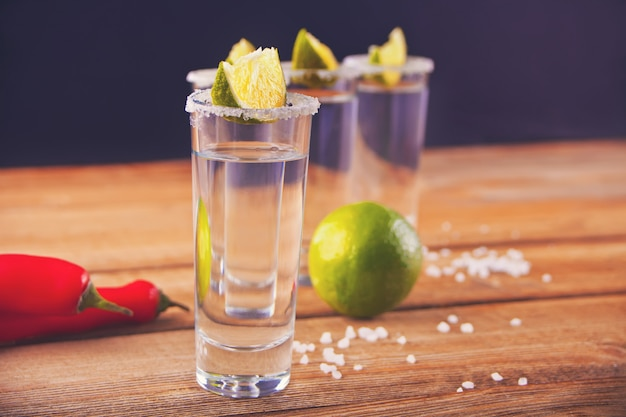 Tequila shot with lime and sea salt on the wooden table