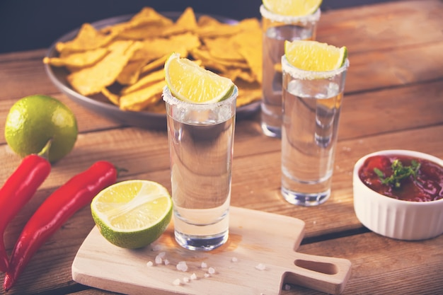 Tequila shot with lime and sea salt on wooden table