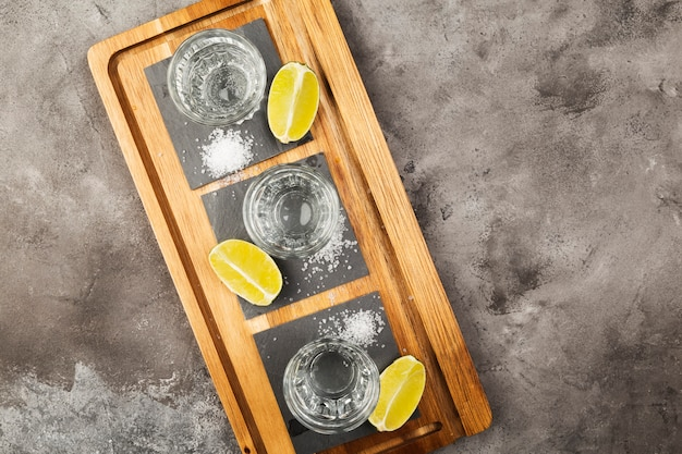 Tequila shots, limes and salt on wooden board on grey space. top view, copy space