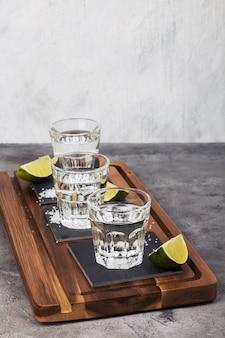 Tequila shots, limes, salt on wooden board