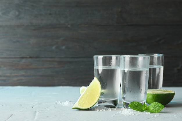 Tequila shots, salt, lime slices and mint on table against wooden