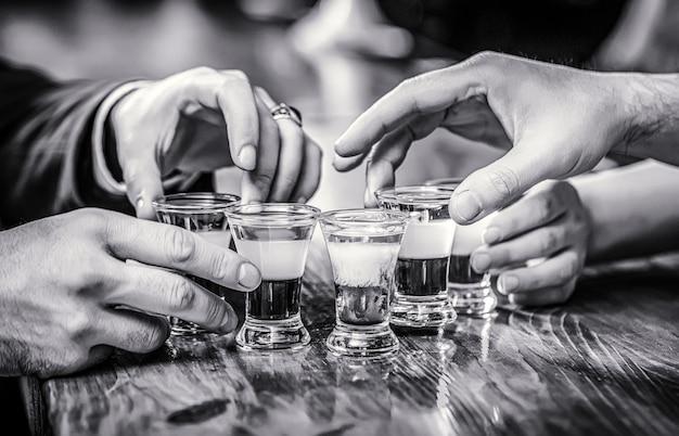 데킬라 샷, 보드카, 위스키, 럼. 나이트 클럽에서 칵테일. 그룹 친구는 바에서 테킬라 글라스를 쐈습니다. 총 또는 리큐어의 남성 손 안경입니다. 검정색과 흰색.