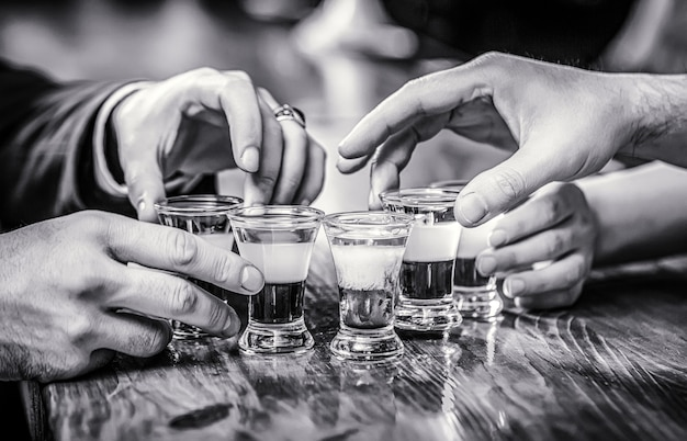Tequila shots, vodka, whisky, rum. cocktail at the nightclub. group friends tequila shot glasses in bar. male hands glasses of shot or liqueur. black and white.