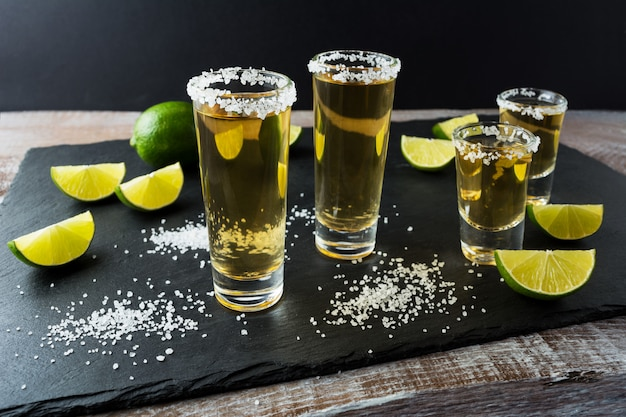 Tequila shots with lime on black stone background