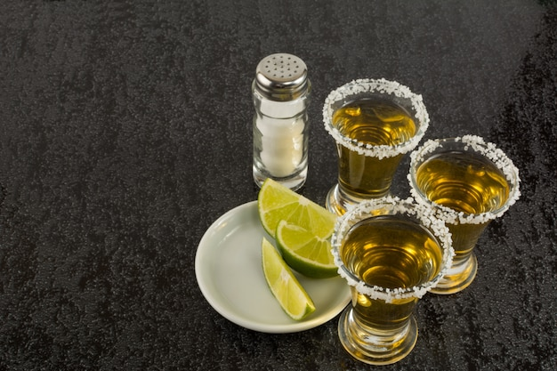 Tequila shots with lime on black